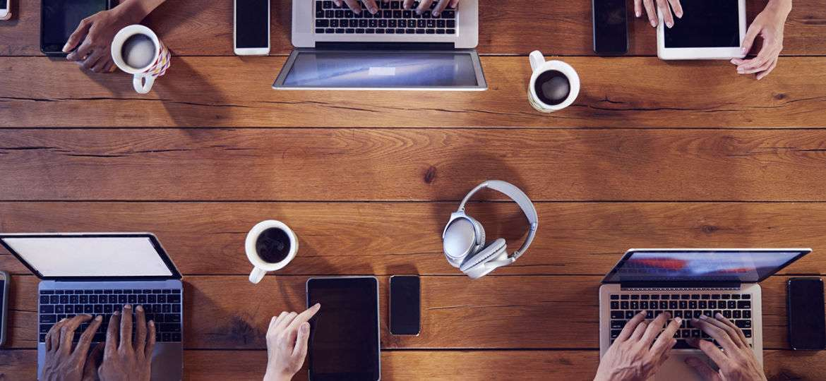 Overhead shot of young adults using technology at a table